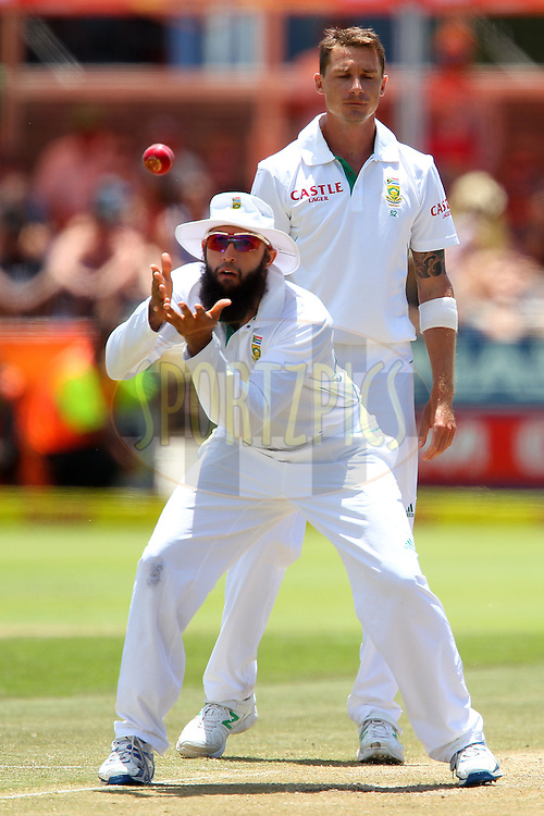 Hashim Amla gathers the ball as Dale Steyn looks on during the 3rd day of the 1st Sunfoil Test match between South Africa and New Zealand held at Newlands Stadium in Cape Town, South Africa on the 4th January 2013..Photo by Ron Gaunt/SPORTZPICS .