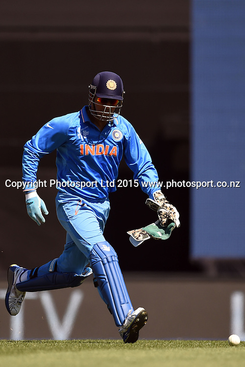 Indian captain and wicket keeper MS Dhoni fields the ball during the ICC Cricket World Cup match between India and Zimbabwe at Eden Park in Auckland, New Zealand. Saturday 14 March 2015. Copyright Photo: Raghavan Venugopal / www.photosport.co.nz