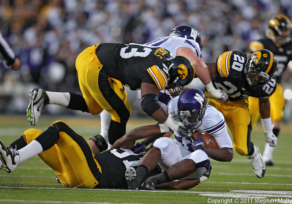 October 15, 2011: Northwestern Wildcats running back Treyvon Green (22) is pulled down by Iowa Hawkeyes defensive lineman Broderick Binns (91) and Iowa Hawkeyes defensive lineman Mike Daniels (93) during the first half of the NCAA football game between the Northwestern Wildcats and the Iowa Hawkeyes at Kinnick Stadium in Iowa City, Iowa on Saturday, October 15, 2011. Iowa defeated Northwestern 41-31.