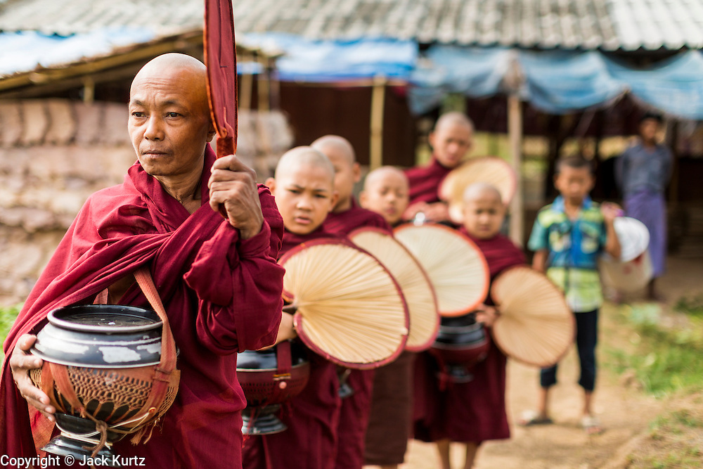 25 MAY 2013 - MAE SOT, TAK, THAILAND: A Burmese monk leads novices out for their morning alms rounds through an unofficial village of Burmese refugees north of Mae Sot, Thailand, on a narrow strip of land about 200 meters deep and 400 meters long that juts into Thailand. The land is technically Burma but it is on the Thai side of the Moei River, which marks most of the border in this part of Thailand. The refugees, a mix of Buddhists and Christians, settled on the land years ago to avoid strife in Myanmar (Burma). For all practical purposes they live in Thailand. They shop in Thai markets and see their produce to Thai buyers. About 200 people live in thatched huts spread throughout the community. They're close enough to Mae Sot that some can work in town and Burmese merchants from Mae Sot come out to their village to do business with them.      PHOTO BY JACK KURTZ