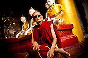 Ein aelterer Moench mit Sonnenbrille. Die Shwedagon Pagode ist das spirituelle Herz von Yangon, wenn nicht ganz Myanmar. Waehrend Myanmar Heimat vielen verschiedenen Religionen ist, sind die Mehrheit der Burmesen Anhaenger des Theravada Buddhismus. Yangon 12ter Mai 2013.