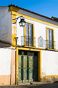 Typical white and yellow house with balcony, lantern, old front door and azulejo blue tiles of religious art in Evora, Portugal