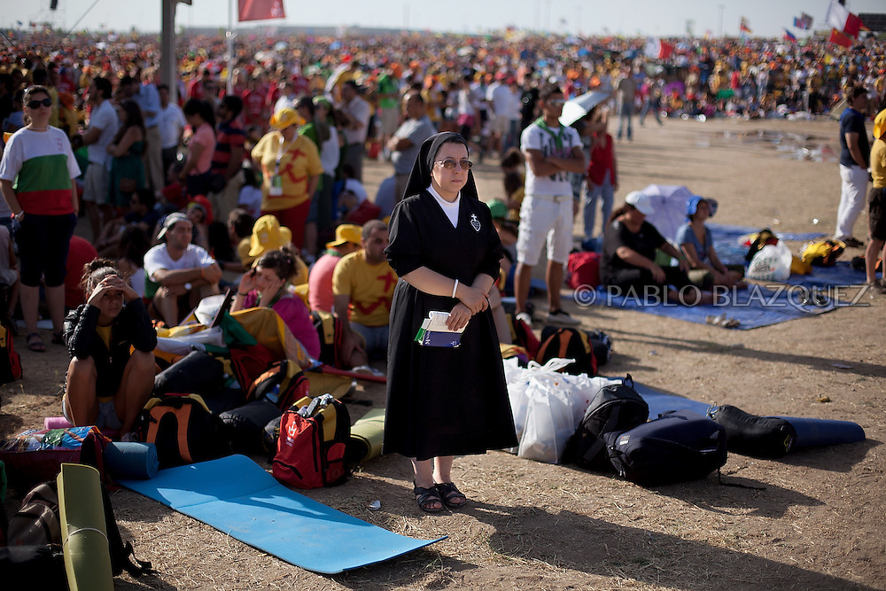 A nun and pilgrims attend a mass celebrated by Pope Pope Benedict XVI at the base of Cuatro Vientos, eight kilometres (five miles) southwest of Madrid on August 21, 2011. The next World Youth Day festival of the Roman Catholic Church will be held in Rio de Janeiro in 2013, Pope Benedict XVI announced Sunday in Madrid