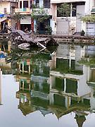 B52 bomber aircraft half submerged in Huu Tiep Lake, houses reflected in water; Ngoc Ha Village; Hanoi; Vietnam