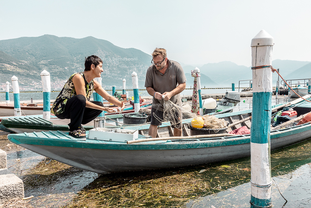iTALY, ISEO LAKE, Clusane,  Gabriella Bosio, talking with a fisherman at the port
