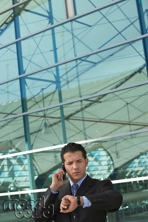Businessman using mobile phone and checking watch outside office building