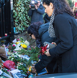 Highgate, London, December 26th 2016. Fans gather outside the London home of pop icon George Michael who died on Christmas day. PICTURED: Women lay flowers at the gate.