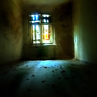 A dark room interior with broken window glass from an old hospital
