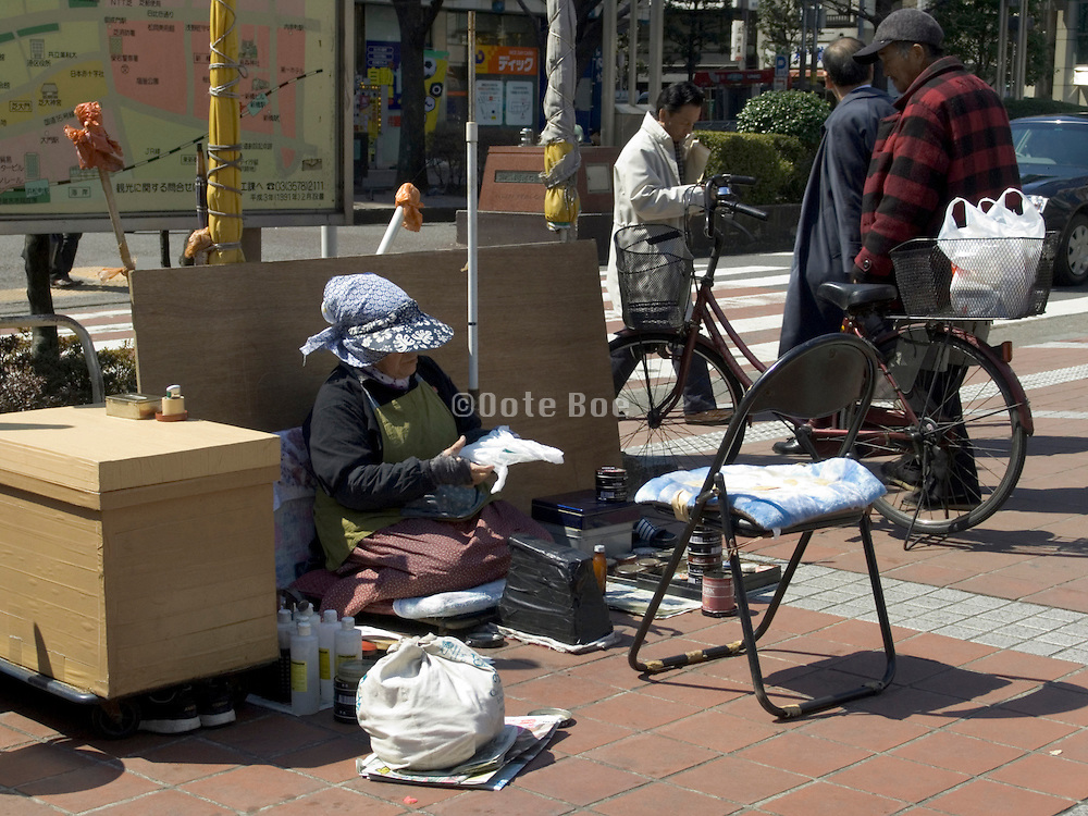 elderly shoe shining lady in the streets of Tokyo