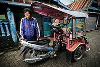 Bapak Sandrey with his becak motor in the Jongaya leprosy settlment, Makassar, Sulawesi, Indonesia. Bapak Sandrey was born in 1963 and has lived in the Jongaya leprosy settlement for 30 years.  He discovered he had leprosy when he was 7 but stayed with his family in Gowa until he was old enough to move to the settlement.  Bapak Sandrey married and had a son in 2003, but his wife died recently.  Since 1987 he has worked as a tukang becak motor driver in Makassar.