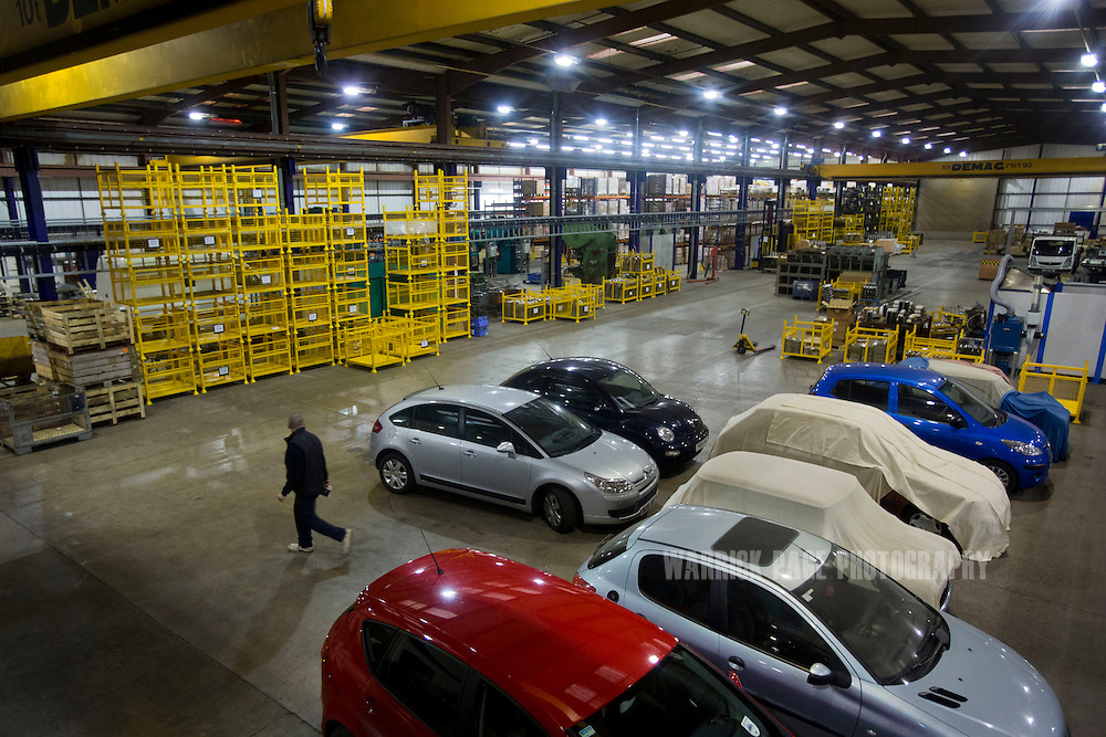 A factory worker walks past test cars in the newly constructed BM Catalysts factory on February 6, 2013, in Mansfield, England. (Photo by Warrick Page)