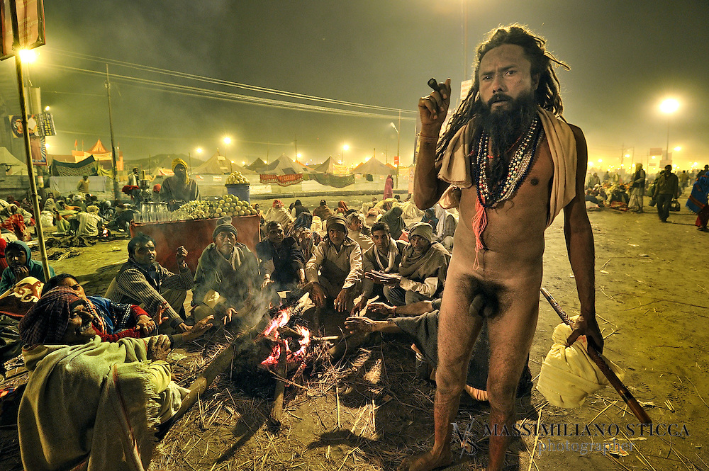 A Naga Sadhu smoking chillum during the Kumbh Mela..The Indian Sadhu's (holy men) have been smoking chillums for thousands of years, and the spiritual meaning of this is comparable to the drinking of red wine by Catholics. At their rituals, the chillum is prepared with a combination of charas (herbs) and tobacco. Through a Hindu ceremony, the Hindu god Shiva was called upon, the Sadhus believing that Shiva would enter into the smoker. In the ceremony, a wet Safi cloth is used, a stone inserted, and the mixture placed into the chillum. The chillum's mouth piece is cupped in two hands and forms a closed prism, as the smoker inhales the smoke without the lips touching the pipe. He puffs violently to light the chillum sufficiently to be passed to the person to the right. In the ceremony of the Jamaican Rastas, the chillum used is made of a cow's horn and wood..