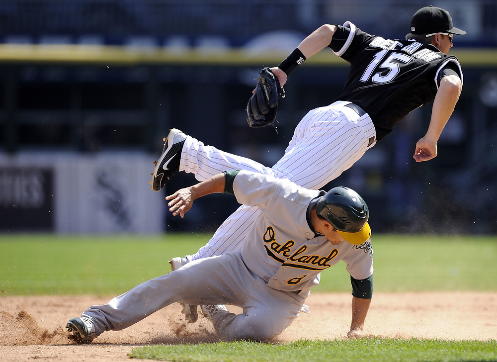 CHICAGO - APRIL 13:  Gordon Beckham #15 of the Chicago White Sox turns a double play over the sliding Kurt Suzuki #8 of the Oakland Athletics on April 13, 2011 at U.S. Cellular Field in Chicago, Illinois.  The Athletics defeated the White Sox 7-4 in ten innings.  (Photo by Ron Vesely)  Subject: Gordon Beckham;Kurt Suzuki