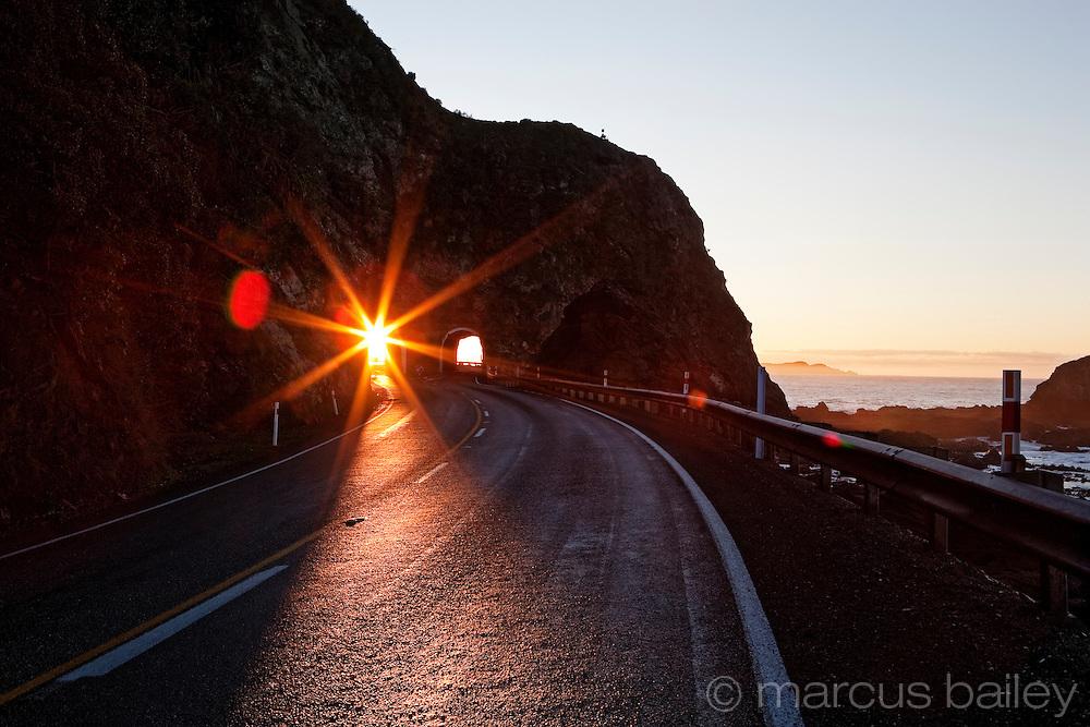 tunnel in rock at sunrise with light through tunnel, nz coast, kaikoura, new zealand