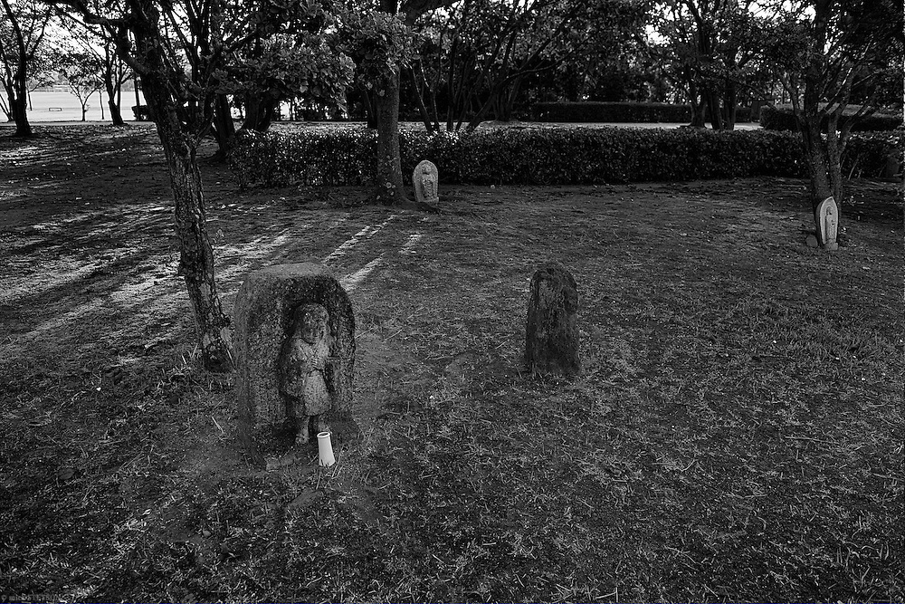 — In the park above the buried toxic sludge, stone statues stand along the shore, reminding those who walk there of the victims that suffered and died from mercury poisoning in Minamata.