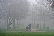 © Licensed to London News Pictures. 21/01/2014. Hammersmith, UK A woman walks across a park. People cross Hammersmith Bridge in heavy fog in West London today 21st January 2014. Photo credit : Stephen Simpson/LNP