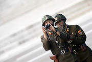 North Korean soldiers film the South Korean side as soldiers of the U.S. and South Korea, Korean War veterans and officials (not pictured) attend a ceremony marking the 60th anniversary of the Korean War ceasefire agreement at the truce village of Panmunjom, north of Seoul July 27, 2013. /Lee Jae-Won