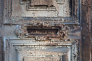 Detail of peeling paint textures on an old, decaying door, on 25th May, 2017, in Lagrasse, Languedoc-Rousillon, south of France. Lagrasse is listed as one of France's most beautiful villages and lies on the famous Route 20 wine route in the Basses-Corbieres region dating to the 13th century.