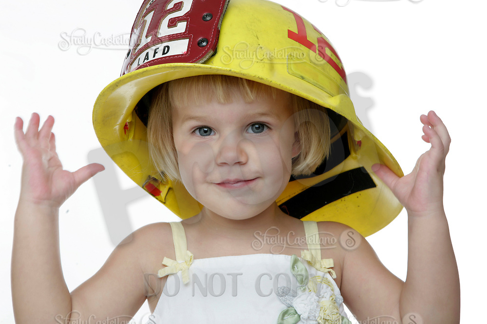 20 July 2008: Two year old young girl Meagan Jennings (2) wears a large Los Angeles Fire Department helmet LAFD station 12 where her daddy works wile  sitting in a chair during a studio shoot against a white background.