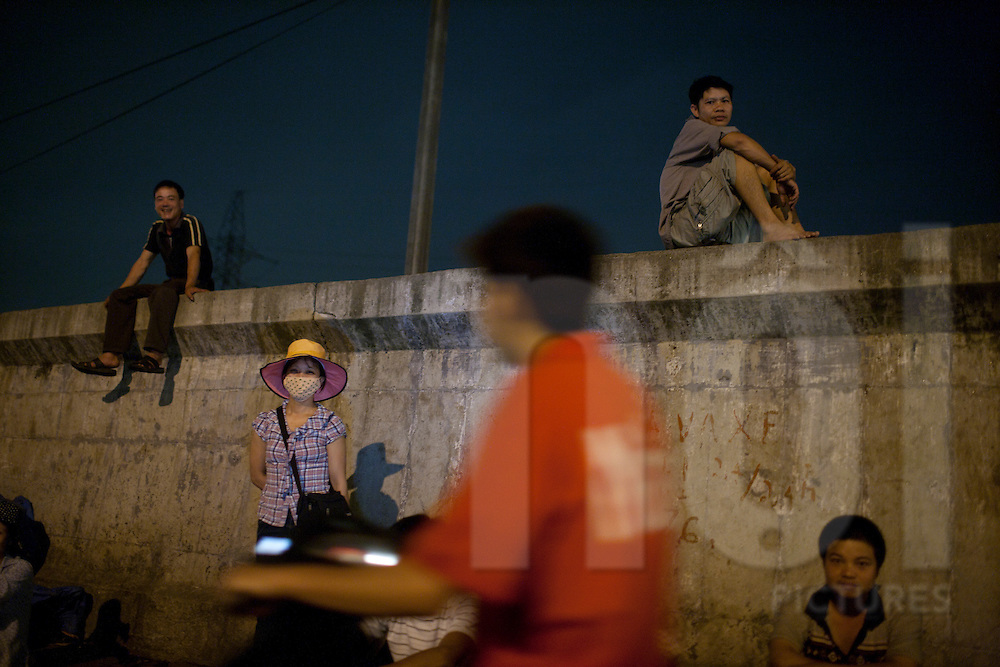 Vietnamese workers sit on top of a concrete dike along the Long Bien Night Market, Hanoi, Vietnam, Southeast Asia