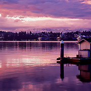 Stormy sky reflections on the water at sunset with cold snow covered Olympic Mountains in the background