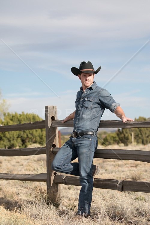 sexy cowboy by a spilt rail fence on a ranch