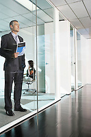 Businessman standing behind glass wall in office interior