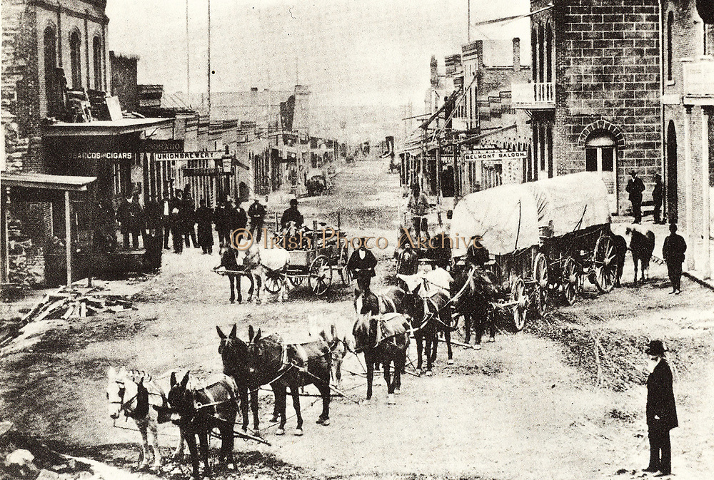 The main street of Helena, 1869, a typical town in the American West with a freight wagon drawn by mules in the foreground and signs for the local Saloon and Brewery further down the street.