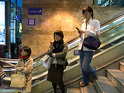 young girls waiting after work for there friends at the entrance of a train station Tokyo