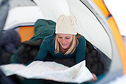 Kate Harvey checks the map from the warmth of her tent and sleeping bag during a winter camping trip in Utah's Wasatch Mountains.