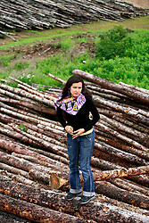 CANADA ALBERTA FORT MCMURRAY 19JUL09 - Greenpeace Canada campaigner Melina Laboucan-Massimo stands next to a large pile of logs from clearcuts at a proposed tarsands site north of Fort McMurray, northern Alberta, Canada...jre/Photo by Jiri Rezac / GREENPEACE..© Jiri Rezac 2009