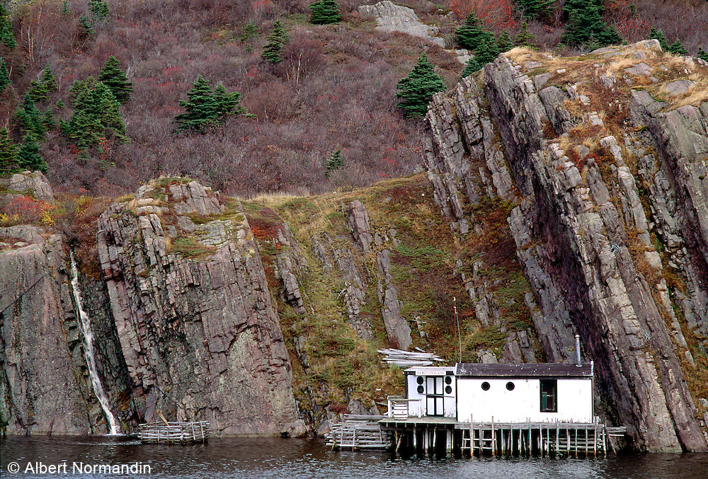 Rock cliff with white building and Newfoundland sign
