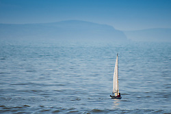 © Licensed to London News Pictures. 15/03/2017. Aberystwyth, Wales, UK. A small sailing dinghy out on the flat calm water of Cardigan Bay on a day of clear blue skies and brilliant unbroken warm springtime sunshine in Aberystwyth Wales .Photo credit: Keith Morris/LNP