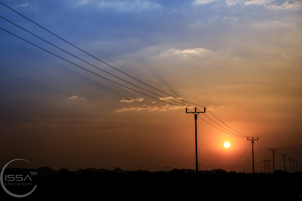 Sun setting over power lines in Oman