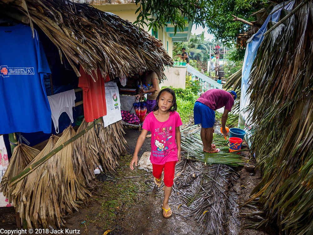 26 JANUARY 2018 - SANTO DOMINGO, ALBAY, PHILIPPINES: A girl walks between thatched huts for evacuees from the Mayon Volcano at Barangay Lidong shelter. The shelter is in school and all of the classrooms are already being used to house evacuees. Recent arrivals are living in tents and huts on the school grounds. The volcano was relatively quiet Friday, but the number of evacuees swelled to nearly 80,000 as people left the side of  the volcano in search of safety. There are nearly 12,000 evacuees in Santo Domingo, one of the communities most impacted by the volcano. The number of evacuees is impacting the availability of shelter space. Many people in Santo Domingo, on the north side of the volcano, are sleeping in huts made from bamboo and plastic sheeting. The Philippines is now preparing to house the volcano evacuees for up to three months.        PHOTO BY JACK KURTZ