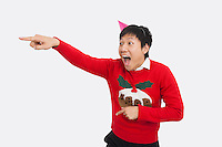 Surprised man wearing Christmas sweater while pointing over white background