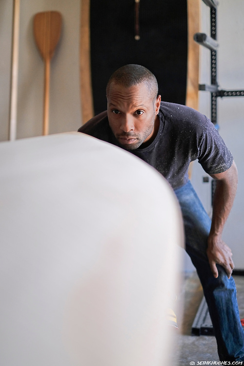 A craftsman with a critical eye checks the shape of his handcrafted, wooden surf board.
