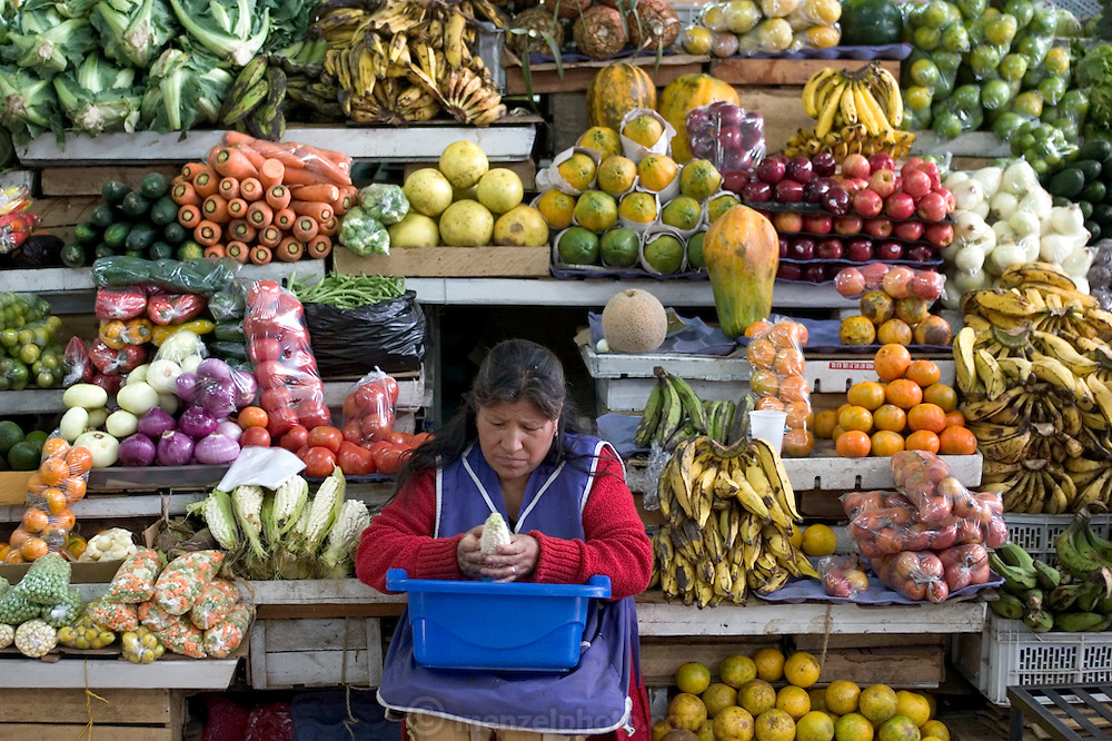 A vendor cleans corn as she waits for customers in the Santa Carolina Market, Quito, Ecuador. (Supporting image from the project Hungry Planet: What the World Eats.)