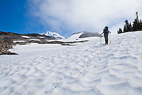 A woman wearing a backpack hiking up a steep snow field in Mount Rainier National Park, Washington, USA.