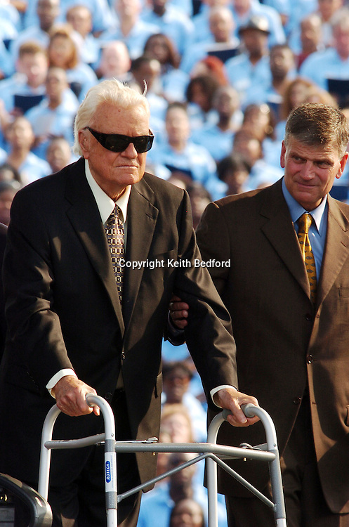 Evangelist Billy Graham(l) is helped to the stage by his son Franklin Graham(r) before speaking during the final day of his Crusade at Flushing Meadows Park in New York June 26, 2005. Graham, 86, has preached the Gospel to more people in a live audience format than anyone in history -- over 210 million people in more than 185 countries. His followers believe that the New York Crusade which runs from June 24 to 26 will be his last live appearance.
