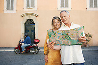 Couple on street looking at map in Rome Italy front view