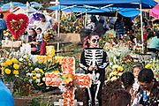 A young girl dressed in a skeleton costume walks through the cemetery during Day of the Dead festival November 2, 2017 in Quiroga, Michoacan, Mexico.  The festival has been celebrated since the Aztec empire celebrates ancestors and deceased loved ones.