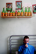 A young scally called Rob Sitting in his bedroom in frony of his drinking trophies, Aberdeen, Scotland, UK 2004