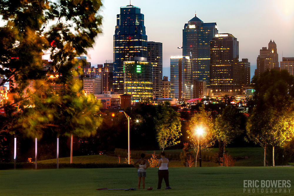 View of Kansas City Missouri downtown skyline at dusk from Hospital Hill Park with two women standing in foreground.