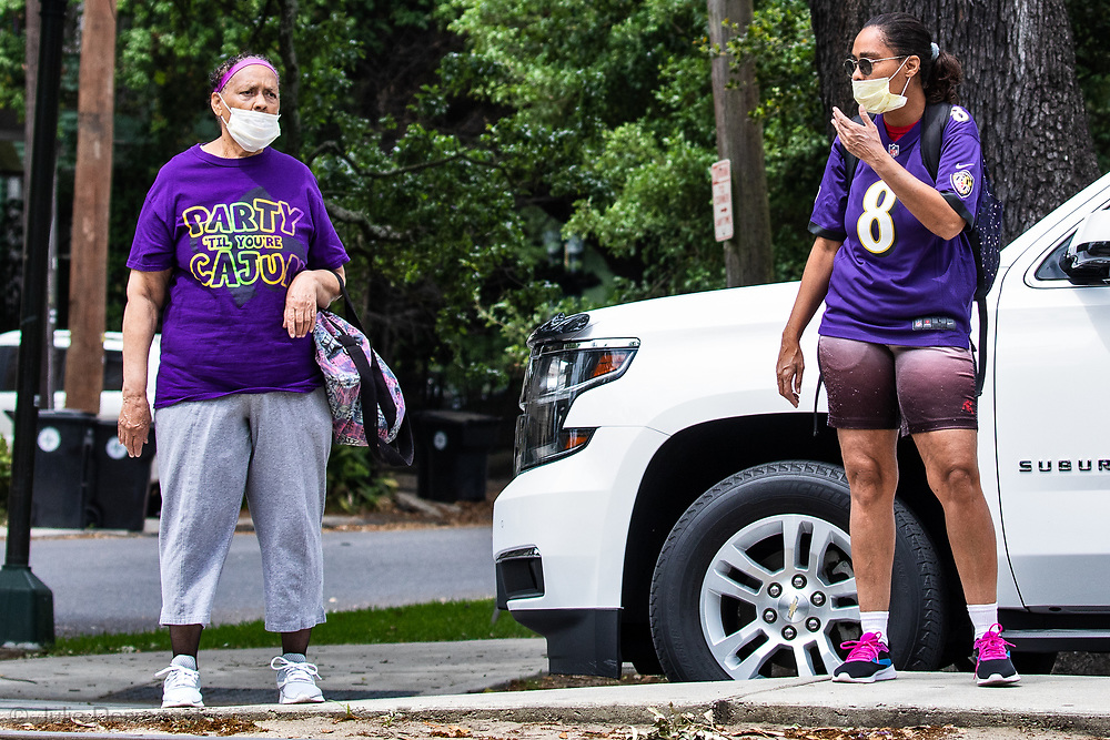 New Orleans,  April 4, 2020,  Womem  wearing masks wait for a streetcar on St. Charles Ave as the Coronavirus continues to spread globaly.