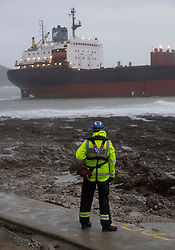 © Licensed to London News Pictures. 18/12/2018. Falmouth, UK. A member of a search and rescue team watches Russian cargo ship Kuzuma Minin, run aground on the reef off Gyllyngvase beach in Falmouth Bay in the early hours this morning. The Falmouth lifeboat and the Coastguard helicopter are involved in the major incident.  Photo credit: Mark Hemsworth/LNP