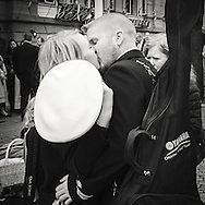 A member of the navey gets a kiss from his girlfriend during the festive events of 17th of May the national holiday of Norway