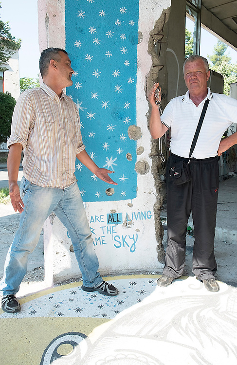"MOSTAR, BOSNIA AND HERZEGOVINA - JUNE 28:  Liubo a Christian ex soldier and Mili a Muslim Taxi driver pose next to a sign ""We are all living under the same sky""  inside a building damaged by 1993 war on June 28, 2013 in Mostar, Bosnia and Herzegovina. The Siege of Mostar reached its peak and more cruent time during 1993. Initially, it involved the Croatian Defence Council (HVO) and the 4th Corps of the ARBiH fighting against the Yugoslav People's Army (JNA) later Croats and Muslim Bosnian began to fight amongst each other, it ended with Bosnia and Herzegovina declaring independence from Yugoslavia.  (Photo by Marco Secchi/Getty Images)"