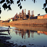 BLAST FURNACES-The once-powerful blast furnaces of Bethlehem Steel Co. contrast with the playful innocence of a young girl as she plays with a stick in the Lehigh River,Bethlehem,PA, at sunset. Copyright 1995-Gregory M. Fota.<br /> (Available for purchase-call for pricing and size)