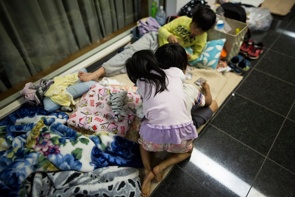 KUMAMOTO, JAPAN - APRIL 19: Young sister embrace her brother inside the Mashiki Town Gymnasium evacuation center on April 19, 2016 in Mashiki, Kumamoto, Japan. This is their fourth day in the evacuation center since magnitude-6.3 quake hit Kumamoto city.<br /> <br /> Photo: Richard Atrero de Guzman